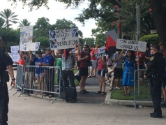 Protesters at a June 18 Donald Trump rally in Houston hold signs while broadcasting Tejano music through a speaker aimed at Trump supporters across the street