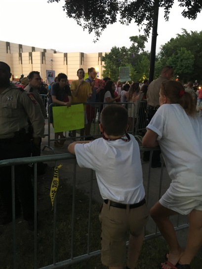 Trump supporters, right, debate protesters, on far side, outside of a rally in The Woodlands June 18 while a law enforcement officer stands between the two sides.
